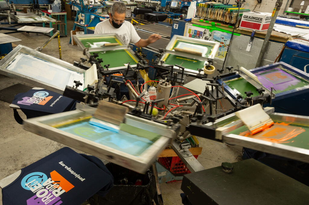 A screen printer operates one of Imprint Revolution's presses.