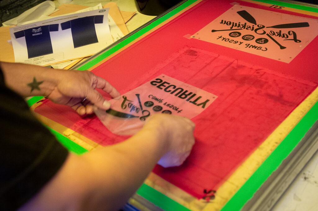 A screen printer carefully places the design on the photo-sensitive screen.