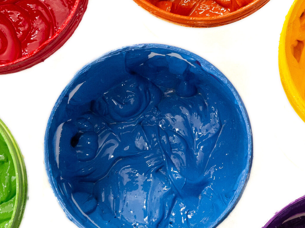 Brightly colored screen printing inks: red, blue, yellow, green.