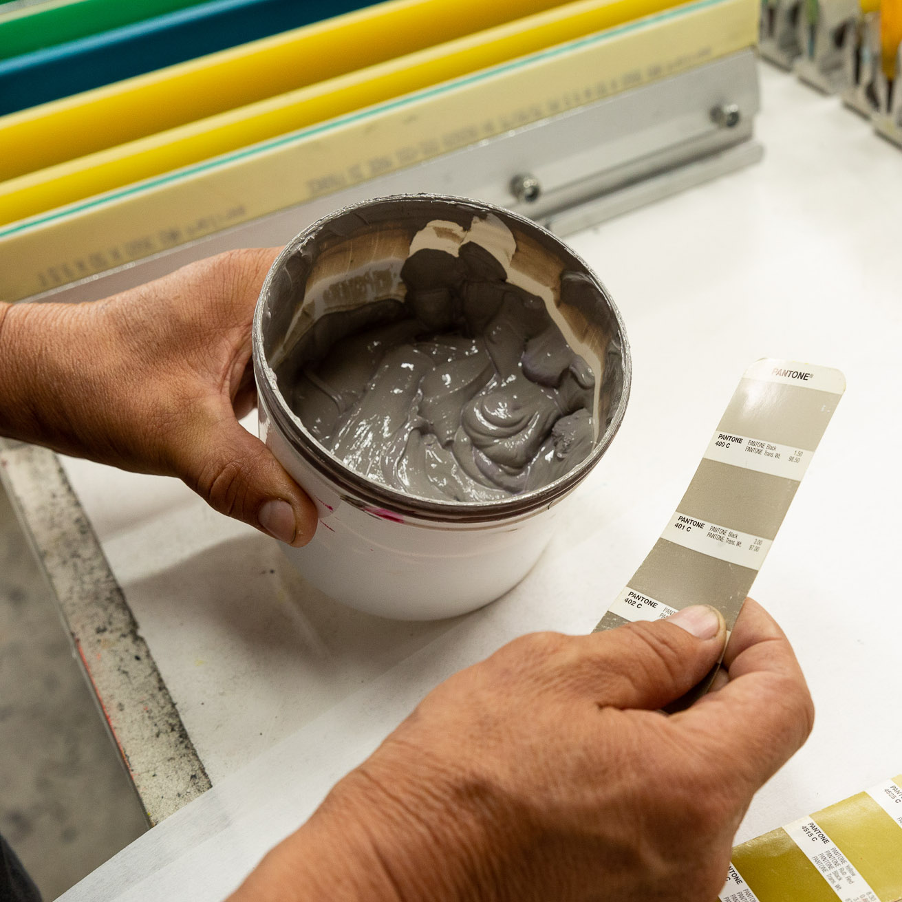 A member of the screen printing team matches ink color to a Pantone swatch.