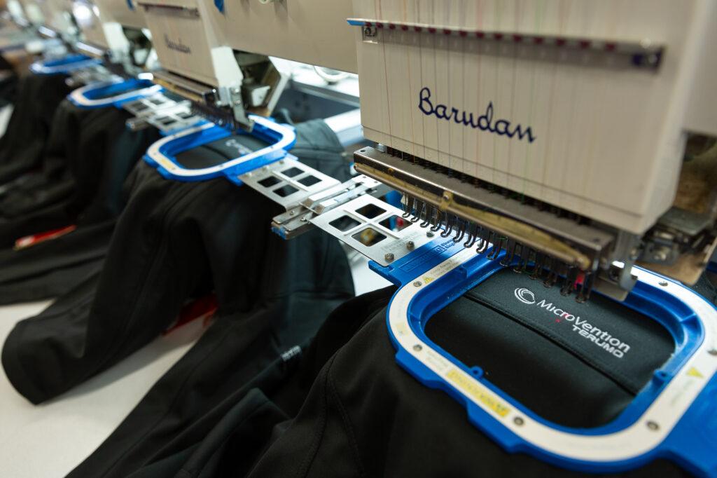 A six-head embroidery machine embroiders a corporate logo onto jackets.