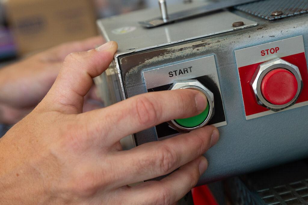 A man presses the start button on a heat press machine.