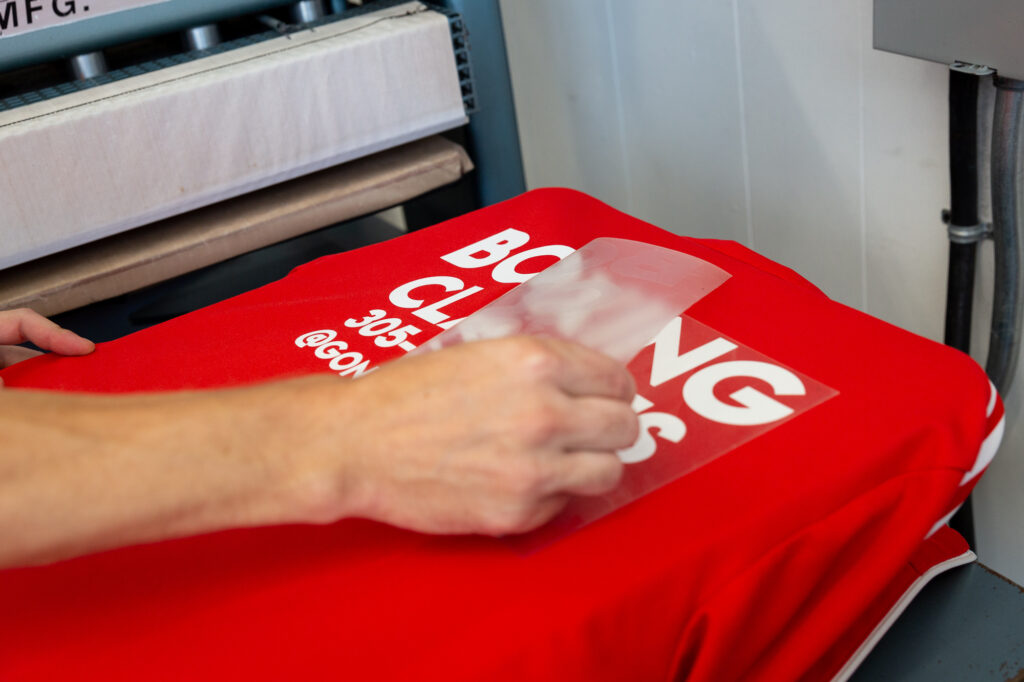 An employee removes the backing material from a vinyl transfer.