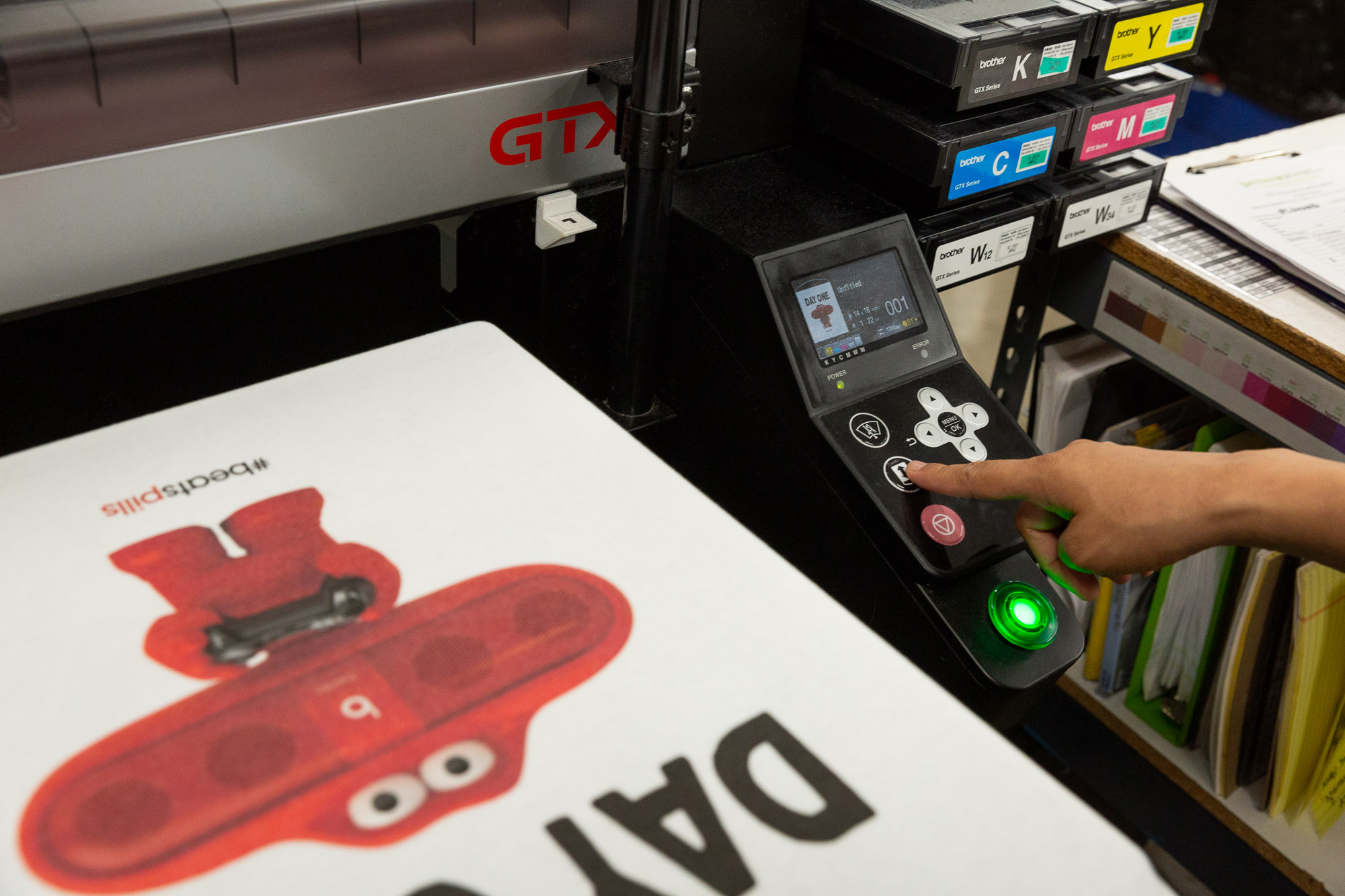 An employee configures settings on the Direct-to-Garment (DTG) printer.