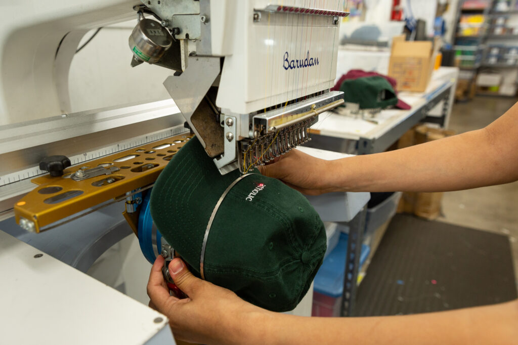 An employee places a hat on an embroidery machine.