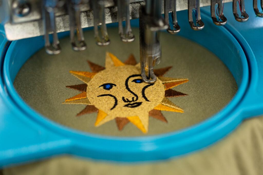 An embroidery machine creates a stylized sun design on a t-shirt.